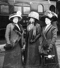 Suffragettes Mrs. Fred Lorenz, Mrs. Ella S. Stewart, and Miss Bertha Seass standing on a railroad platform.  (Chicago History Museum)