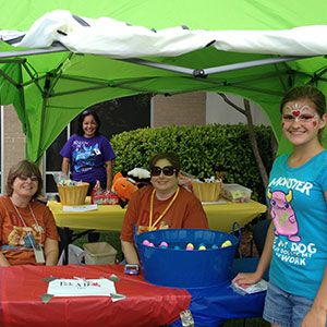 Beauregard Parish Library staff and a preteen patron prepare for the 2013 SRP Kickoff Carnival.