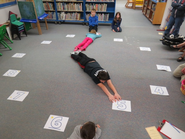 Kids play a time-telling game in the Crazy 8s Math Club.