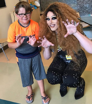 Drag Queen and child face camera and hold hands up in front of them smiling.