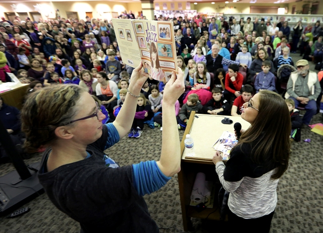 "An art teacher from Madison, Wis., holds up a copy of ""I Am Jazz"" to the crowd as co-author Jessica Herthel reads aloud."