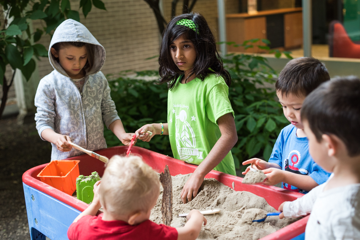 Kids playing with a sand table.