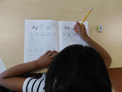 A girl practices writing the letter H in a cursive practice workbook