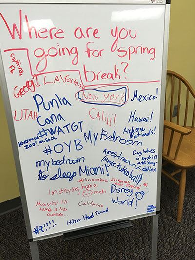 "Writing on a whiteboard asking, ""Where are you going for spring break?"" with responses"