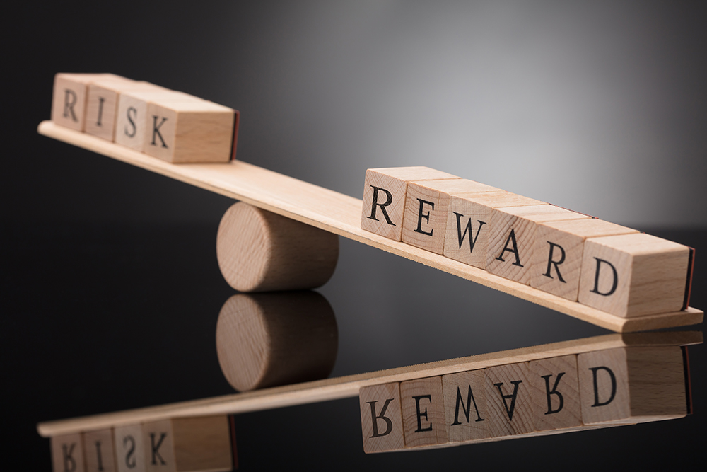 "Word tiles that read ""risk"" and ""reward"""