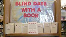 "Books on a table covered in plain wrapping paper with a the first line written on the front. A sign that says ""Blind Date With a Book"" is behind the table."
