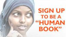 """A woman looks to her right at the words, """"Sign up to be a 'human book.'"""""""