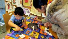 Participants mix paint colors for their paper plate self-portrait.