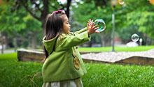 A young girl playing with bubbles in a park
