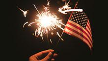 Hand holding a sparkler and a US flag