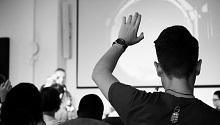 person raising hand during presentation