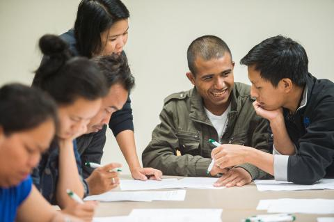 Experts from ASIA Inc. teach financial literacy to a Nepali-speaking man.
