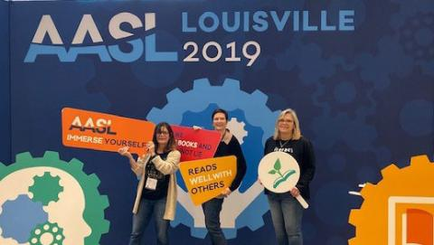 Three women standing in front of AASL Conference sign