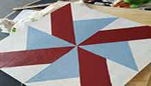 Wooden square painted to look like a quilt square