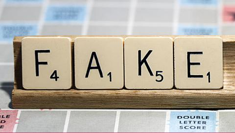 "Scrabble tiles that spell out ""fake"""