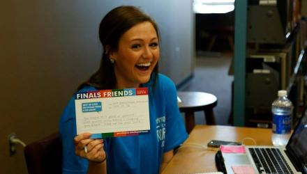 Student holding finals friend card