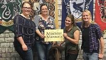 """Four people pose with """"Mischief Managed"""" sign"""