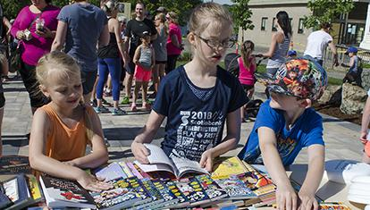 Three young children browsing books on a table at an outdoor event.