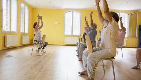 Group of senior citizen women do chair yoga.