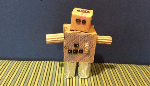 A robot sculpture made from cardboard and mixed materials.