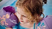 Girl wearing swim floaties. Photo by Jelleke Vanooteghem on Unsplash