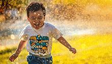 Child running through sprinklers photo by MI PHAM on Unsplash