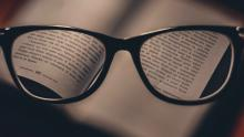 Glasses magnifying the text on the page of a book
