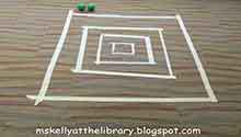 "A Skeeball game board taped to the floor, and two balls (from the activity ""Tape Games"")"