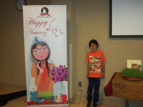 Child poses with Nowruz banner
