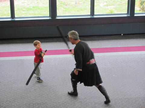 A child fights against an adult with a toy sword.