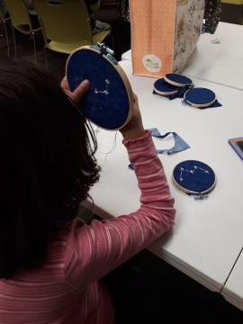 Child working on cross-stitch