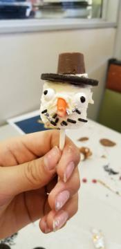 Hand holding a marshmallow on a stick, with decorations to make it look like a snowman.