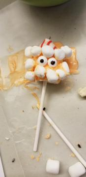 Candy on a stick with marshmallows to look like a face.