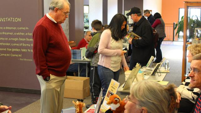 Local Author Fair patrons visiting tables