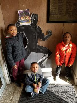 Three kids stand and smile in front of superhero cardboard cutout