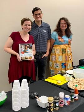 Three people standing behind a table with food to prepare