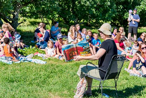 Librarian reading to crowd in the orchard