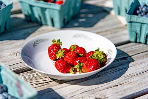Strawberries on a white plate sitting on a picnic table