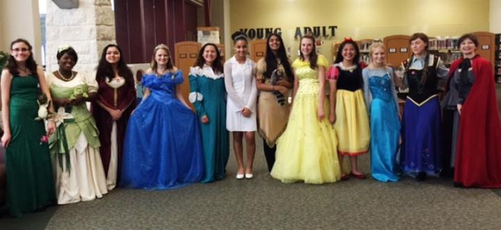 Twelve women dressed as princesses stand together and smile for the camera.