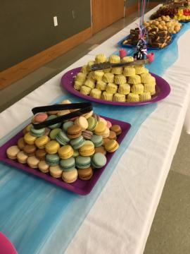 A long table for food and refreshments includes macaroons, small cakes, fruit and more.