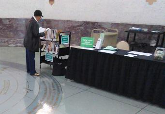 A woman reads a book while standing next to the greeting table.