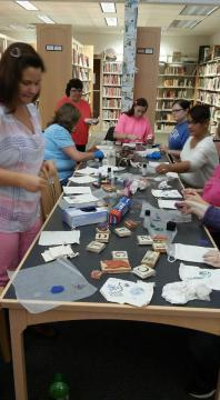 The participants use stamps to decorate linen gift bags.