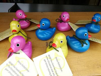 """Photo of a group of rubber ducks with notes attached saying """"Stress ReDUCKtion QUAK! You found me! Head down to the Circulation desk and claim your stress reducing prize!"""""""