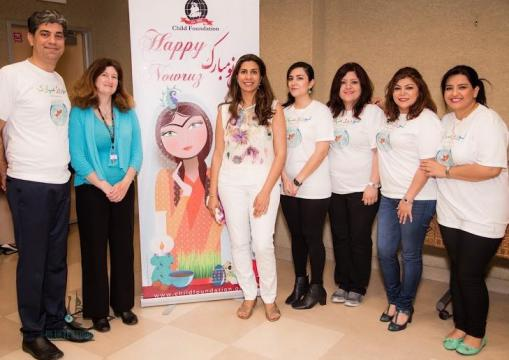 Nowruz Celebration planners and volunteers in front of banner
