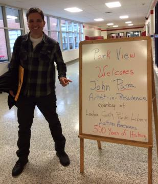 Writer John Parra in front of event signboard