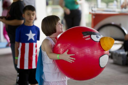Girl holding large red ball decorated with Angry Bird face
