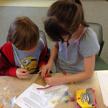 Two participants collaborate on modeling clay for their stop-motion movie.