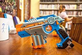 A nerf phaser that is used for laser tag rests on top of a table.