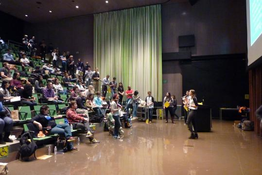 A woman addresses a large auditorium filled with people.