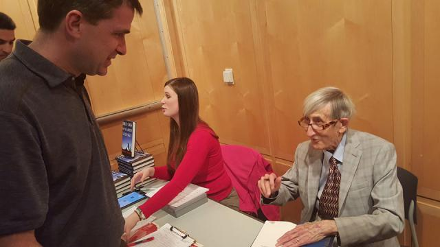 Freeman Dyson sits down as he signs the book of a man standing in front of him.